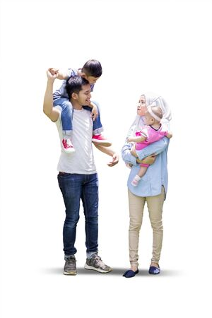 Photo pour Full length of muslim parents and their children walking together in the studio, isolated on white background - image libre de droit