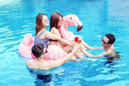 Photo pour Group of young people making drinks toast with inflatable flamingo on the swimming pool - image libre de droit