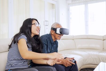 Photo for Side portrait of beautiful Asian woman sitting on a sofa with her old father, while guiding him how to play vr glasses in their living room - Royalty Free Image