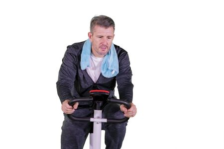 Photo pour Portrait of grey hair man doing exercise while sitting on bike stationary in studio, isolated on white background - image libre de droit