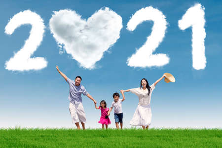 Photo pour Happy family running on the meadow while holding hands together with clouds shaped number 2021 and heart symbol in the blue sky - image libre de droit