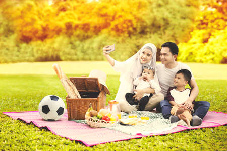 Photo pour Muslim family using a cellphone to taking a selfie photo together while picnicking in the park with autumn trees background - image libre de droit
