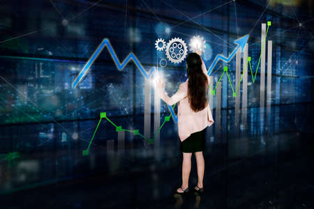Photo for Rear view of female manager working with financial chart on virtual screen while standing with double exposure of nigh city background - Royalty Free Image