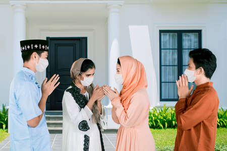 Photo pour Four young people wearing face mask while give greet hands to forgive each other during Eid Mubarak celebration in the house yard - image libre de droit