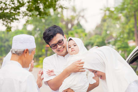 Photo pour Three generation Muslim family looks happy while standing together during Eid Mubarak on the road - image libre de droit