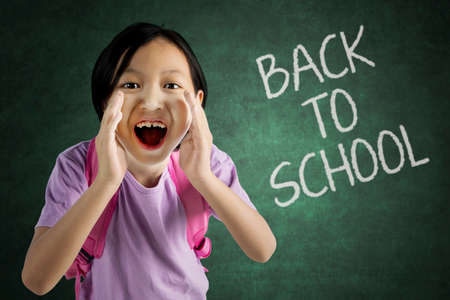 Photo for Picture of cute schoolgirl announces back to school by screaming in the classroom - Royalty Free Image