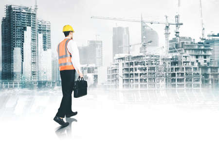 Photo pour Rear view of male engineer carrying a suitcase while walking toward construction site project - image libre de droit