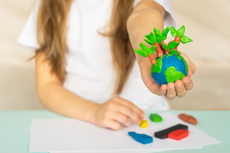 Foto per A small globe with trees in the hands of a child. Layout of the planet made of plasticine in children's palms. Concept ecology. Copy space. Horizontal frame. - Immagine Royalty Free