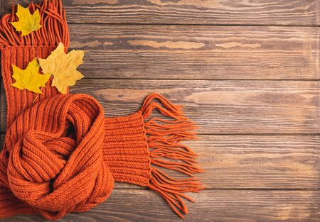 Foto per A bright knitted orange knitted scarf and maple leaf lies on a wooden background. Horizontal frame. Autumn concept - Immagine Royalty Free
