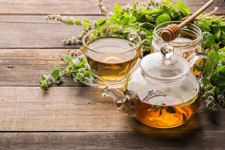 Photo pour Tea with fresh leaves of lemon balm mint in a cup and teapot on a wooden rustic background. Healing herbal drink. - image libre de droit
