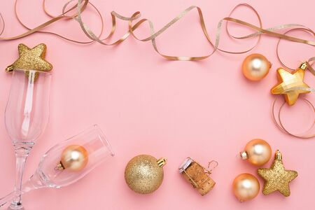 New Year or Christmas flat layout. Festive shiny balls cones serpentine empty wine glasses on a pink background.