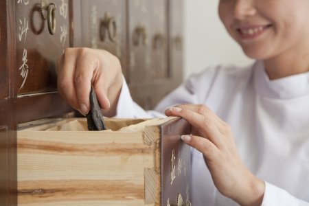 Doctor Taking Herb Used for Traditional Chinese Medicine Out of a Drawer