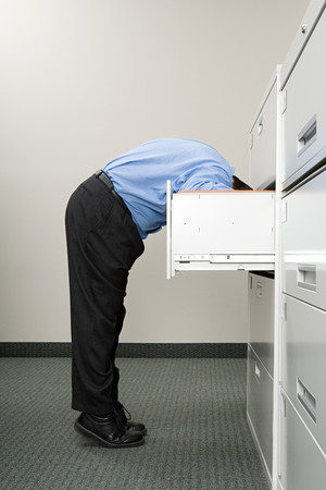 Man looking in filing cabinet