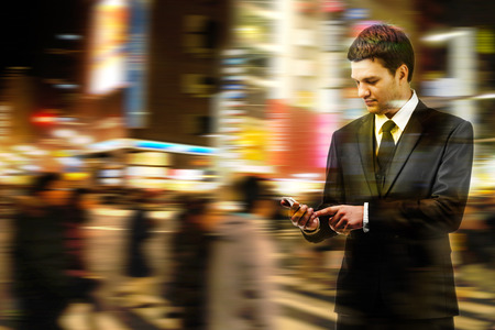 Double exposure of businessman uses the smart phone on the city street, and motion blur background