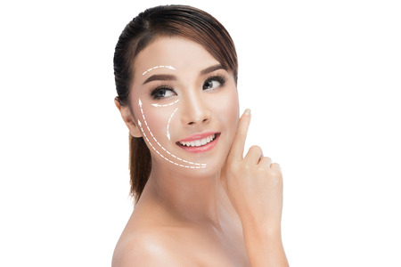 Foto de beauty, plastic surgery, aging, people and health concept - beautiful young woman touching her face with lifting arrows isolated on white with clipping path - Imagen libre de derechos