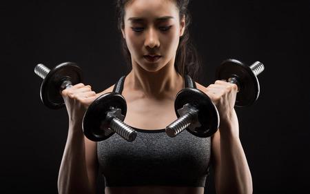 Photo pour Beautiful girl exercising squatting with dumbbells on black. - image libre de droit