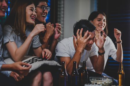 Foto de Young fans watching sports on TV with beer and snacks,friendship, drink, alcohol, holidays and people concept - Imagen libre de derechos