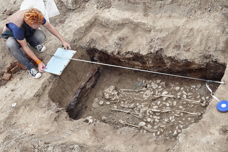 Photo pour Archaeological excavations. Young stylish archaeologist with red hair makes drowings of human bones, skeleton and skull in the ground tomb. Real digger process. Outdoors, copy space. - image libre de droit