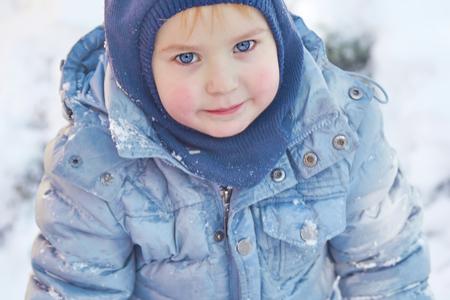 Foto de Hat and hoodie on winter background. Healthy childhood. Outdoors, winter activity. Copy space, close up portrait. - Imagen libre de derechos