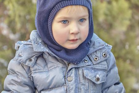 Foto de Winter clothes and hat (hood) on green background. Healthy childhood. Outdoors, copy space, close up portrait. - Imagen libre de derechos