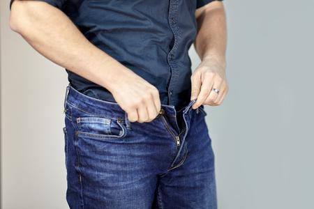 Photo pour Man unzipps blue jeans. Man torso, fingerring, blue shirt, casual wear. Indoors, grey empty background, copy space. - image libre de droit