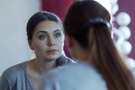 Foto de Reflection of a young attractive caucasian woman looking into a mirror. Wearing casual, beautiful blue eyes, serious look. Indoors, copy space. - Imagen libre de derechos
