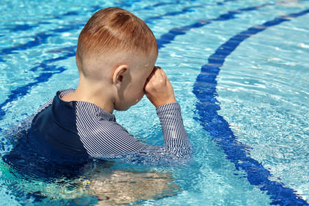 Photo pour Little boy with blond hair rubs eyes with hands in summer swimming pool, or cries, back to the camera. Water drops on head and face, wet T-shirt, blue color of water background. Sunny day, copy space. - image libre de droit