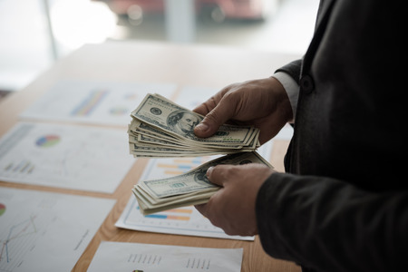 Young asian businessman standing count a dollar bill from his desk. The concept of business results