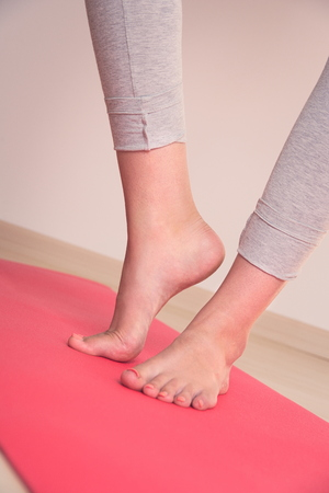 Foto de Teen Girl's Feet on Red Yoga Mat Closeup - Imagen libre de derechos