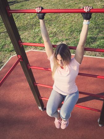 Photo for Young Athletic Woman Exercising on Wall Bars in the Park - Royalty Free Image