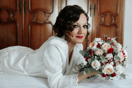Foto de Bride with a bouquet of wedding flowers lying on the bed. Attractive young bride lies next to the dress and winter bouquet. Morning bride in a luxury hotel - Imagen libre de derechos
