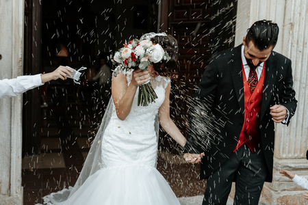 Foto de People throw rice on newlyweds walking out of the church. Beautiful wedding tradition. - Imagen libre de derechos
