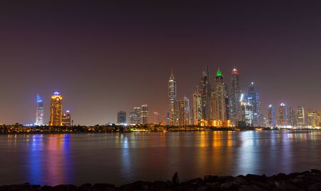 Photo pour Dubai skyline at night with lights on the water and luxirious skyscrapers of UAE. Modern architecture of the future. - image libre de droit