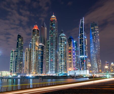 Photo for Dubai skyline at night with lights on the water and luxirious skyscrapers of UAE. Modern architecture of the future. - Royalty Free Image