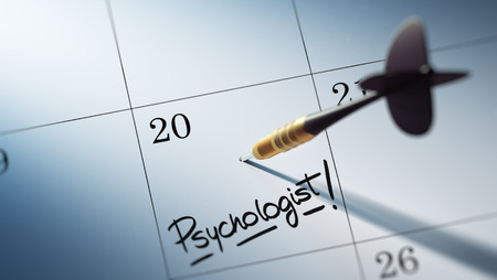 Concept image of a Calendar with a golden dart stick. The words Psychologist written on a white notebook to remind you an important appointment.