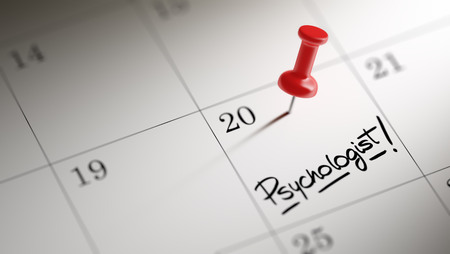 Concept image of a Calendar with a red push pin. Closeup shot of a thumbtack attached. The words Psychologist written on a white notebook to remind you an important appointment.