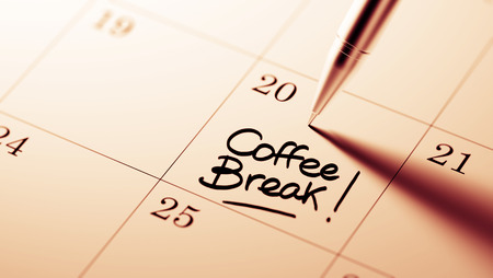 Closeup of a personal agenda setting an important date written with pen. The words Coffee Break written on a white notebook to remind you an important appointment.