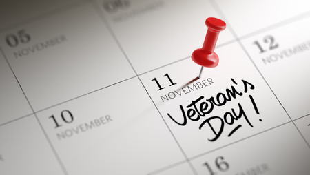Concept image of a Calendar with a red push pin. Closeup shot of a thumbtack attached. The words Veteran\'s Day written on a white notebook to remind you an important appointment.