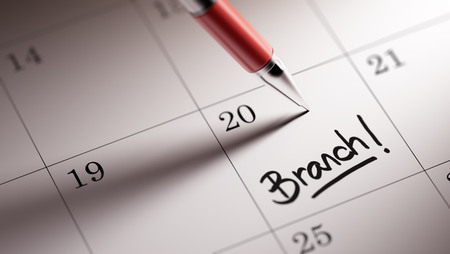 Closeup of a personal agenda setting an important date written with pen. The words Branch written on a white notebook to remind you an important appointment.