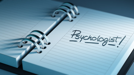 Closeup of a personal agenda setting an important date representing a time schedule. The words Psychologist written on a white notebook to remind you an important appointment.