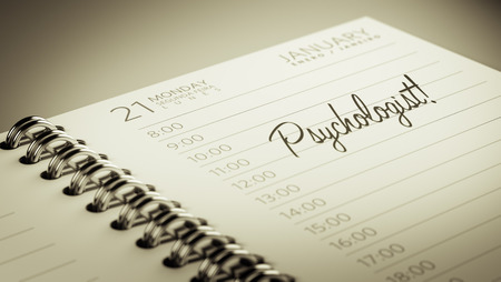 Closeup of a personal calendar setting an important date representing a time schedule. The words Psychologist written on a white notebook to remind you an important appointment.