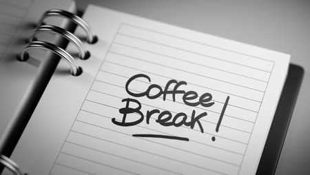Closeup of a personal agenda setting an important date representing a time schedule. The words Coffee Break written on a white notebook to remind you an important appointment.