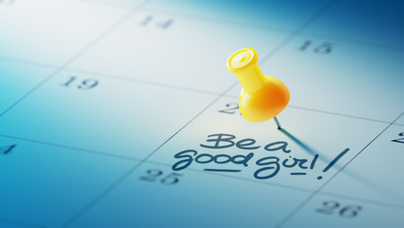 Concept image of a Calendar with a yellow push pin. Closeup shot of a thumbtack attached. The words Be a good girl written on a white notebook to remind you an important appointment.