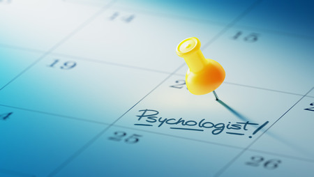 Concept image of a Calendar with a yellow push pin. Closeup shot of a thumbtack attached. The words Psychologist written on a white notebook to remind you an important appointment.