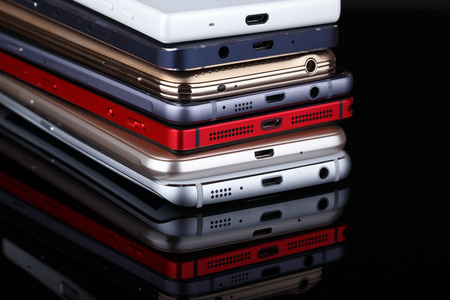 Mobile phone wireless communication technology and mobility business office concept - group of smartphones on black background