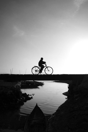 Silhouette of lonely young boy riding bicycle on small bridge cross the river at morning, he ride bike leisure,  this make sad, calm scene at countryside