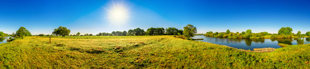 Landscape in summer with trees, meadows, river and sun