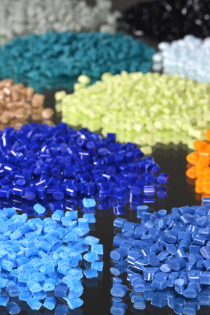 some heaps of dyed polymer granulate for injection moulding