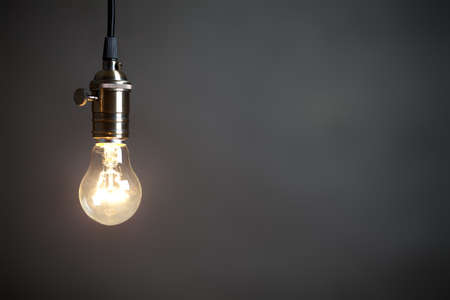 Foto de Vintage incandescent light bulb on gray background. On right is empty space to put text or something else. This file is cleaned and retouched. - Imagen libre de derechos