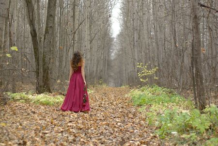 girl in a red dress walking in the forest